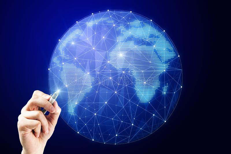 AI and network concept. Hand pointing at creative glowing polygonal globe on dark background. AI and network concept royalty free stock image