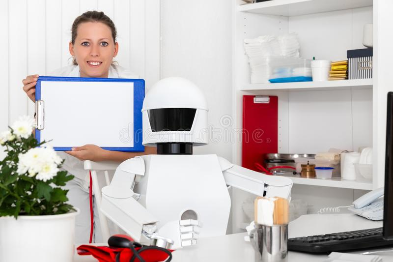 Ai robot as professional doctor in his office. Sitting behind the desktop, nurse or second female doctor with clipboard in her hands royalty free stock images
