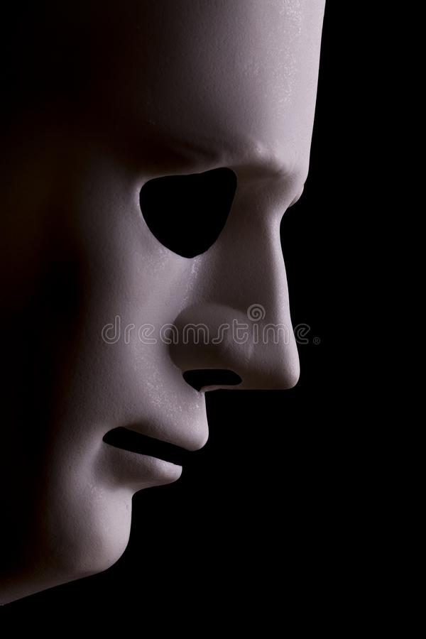 AI robotic face profile close up blank. Robot face mask side view close up with textured skin and blank eyes. Black background and space for text. Artificial royalty free stock photography