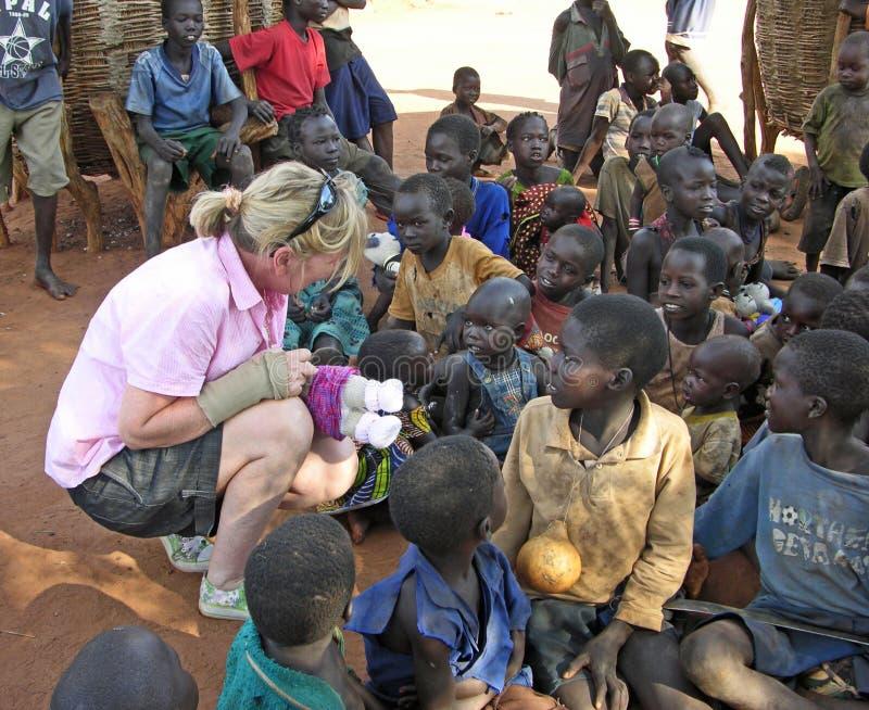 Aid worker brings hope to smiling African children in village Uganda stock image