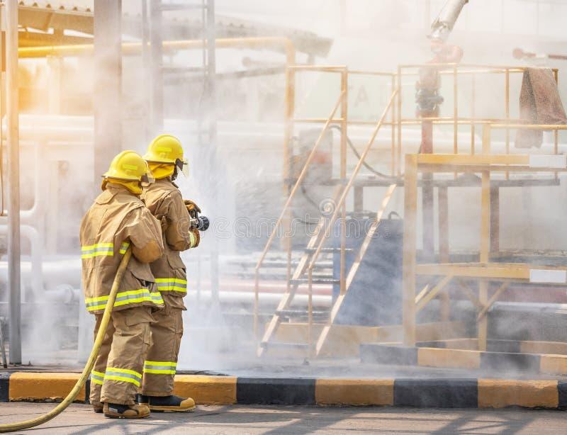 Aide courageuse d'équipe d'ami de firemans professionnels dans le bec jaune de tuyau d'incendie de participation d'uniforme de po images libres de droits