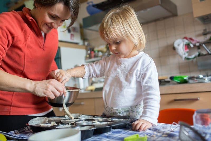 Aide de fille de b b faisant cuire avec sa maman dans la for Aide de cuisine