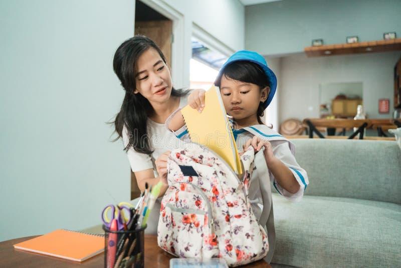 Aide de maman sa petite fille préparant la substance d'école sur le sac à dos de ses daughtes photos stock