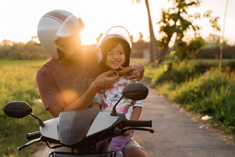 Aide de papa sa fille pour attacher le casque image libre de droits