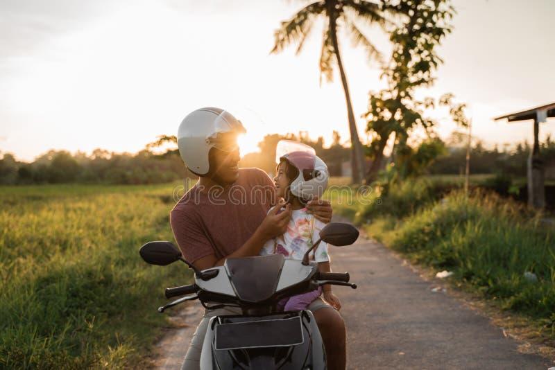 Aide de papa sa fille pour attacher le casque images libres de droits
