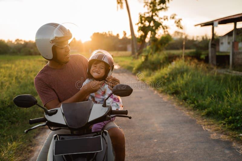 Aide de papa sa fille pour attacher le casque photo stock