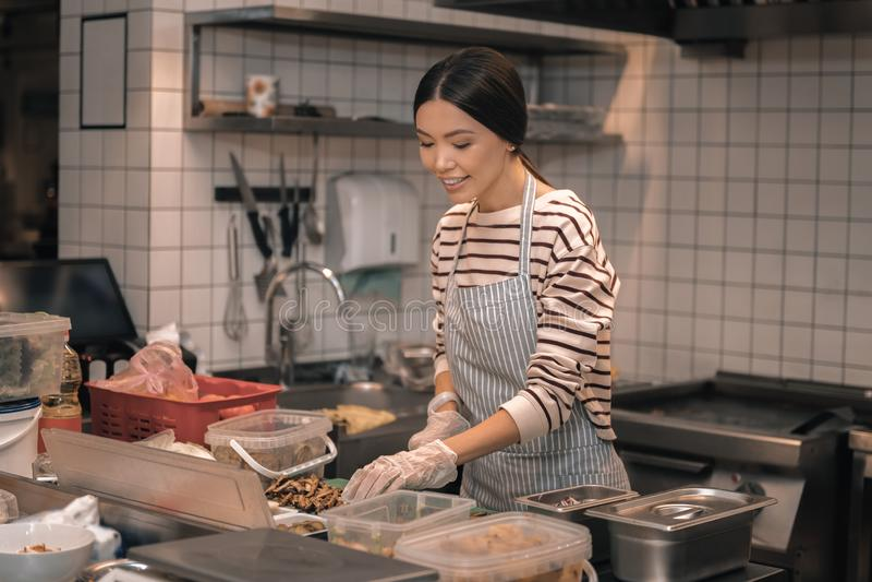 Aide des gants de port de chef coupant la nourriture pour des salades photos stock