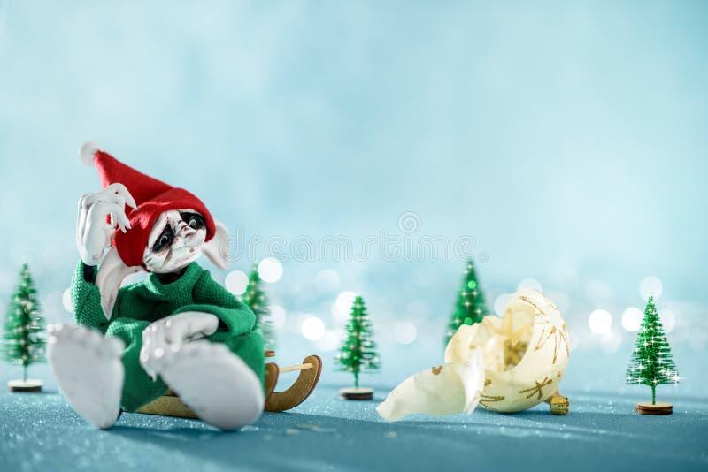 Aide triste Elf de Santa se reposant sur le traîneau regardant la babiole cassée de Noël Scène de Noël de Pôle Nord L'atelier de  image stock