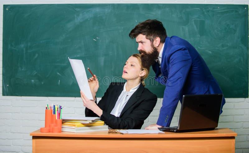 Aidez-moi avec des documents Professeur et surveillant travaillant ensemble dans la salle de classe d'école Programme d'enseignem images libres de droits