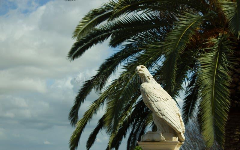 Aigle en pierre blanc contre les branches de ciel bleu et de palmier photo stock
