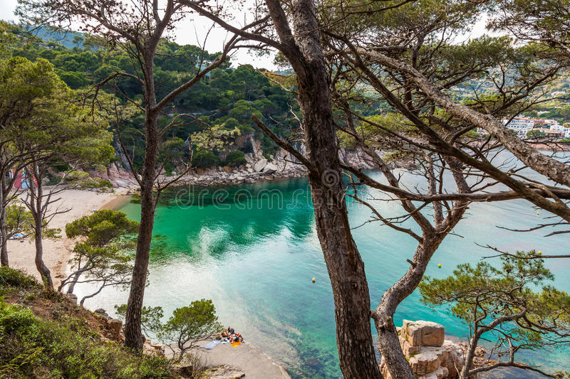Aiguablava beach and bay. BEGUR, COSTA BRAVA, SPAIN - JUNE 6: Tourists enjoying the beach of Aiguablava, one of the most beautiful bays in Spain, with clear royalty free stock photos