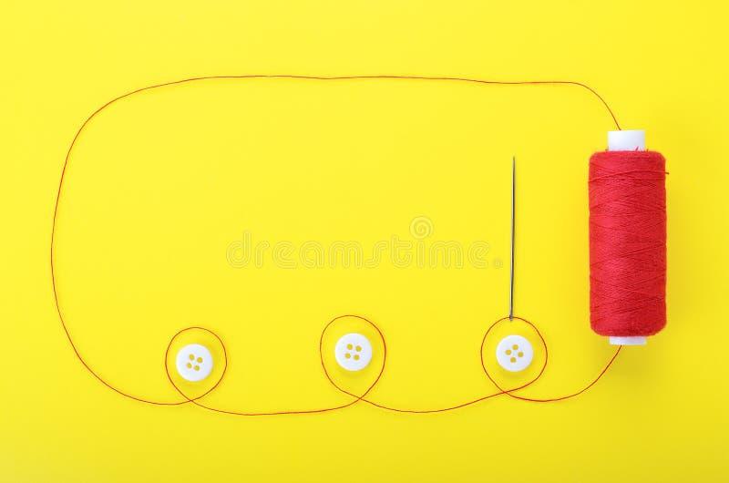 Aiguille avec les boutons rouges de fil et d'habillement photo libre de droits