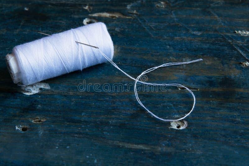 Aiguille blanche de fil et de couture sur le fond bleu rustique avec l'espace pour le texte Outils de couture minimaux images stock