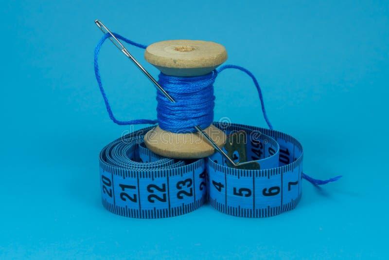 Aiguille bleue de fil, de ruban métrique et de couture image stock