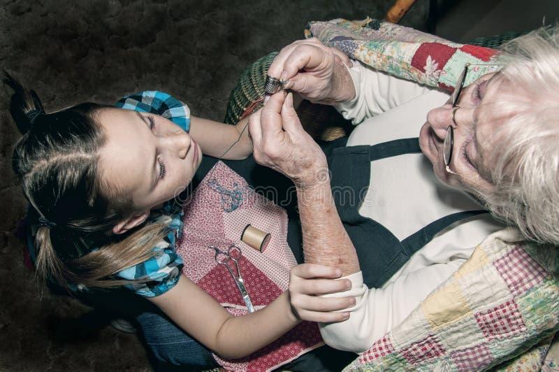 Aiguille de aide de fil de grand-mère de fille photographie stock libre de droits
