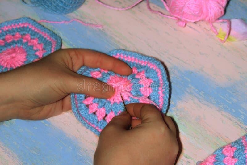 Aiguille des mains des femmes le modèle sur le produit tricoté image stock