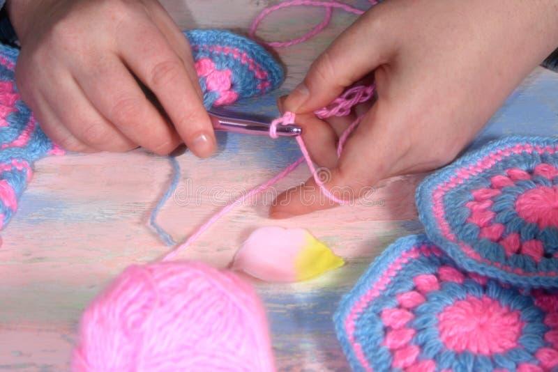 Aiguille des mains des femmes le modèle sur le produit tricoté images stock