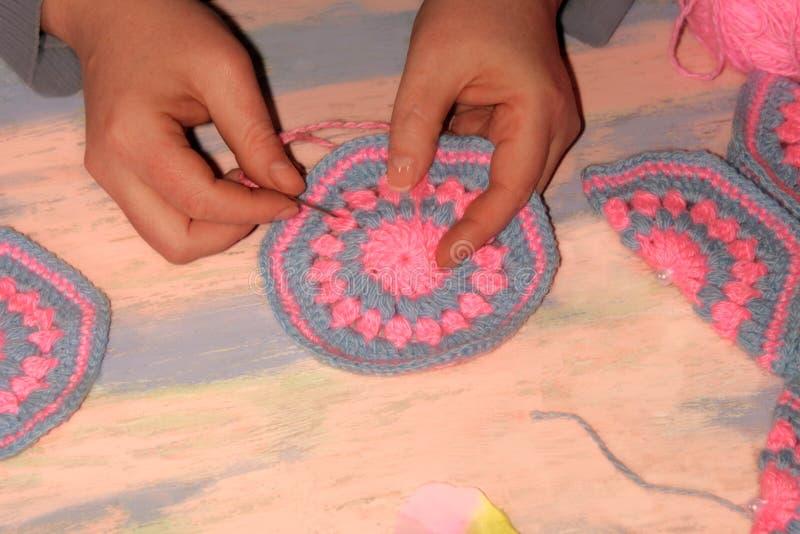 Aiguille des mains des femmes le modèle sur le produit tricoté images libres de droits