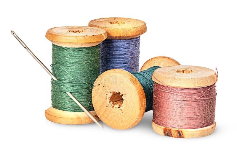Aiguille et fil multicolore sur la bobine en bois photos stock