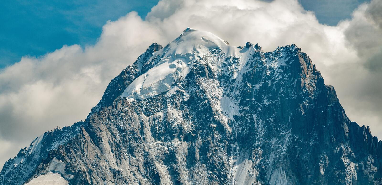 Aiguille Verte in close-up with snow topped mountain and clouds in the background stock photography