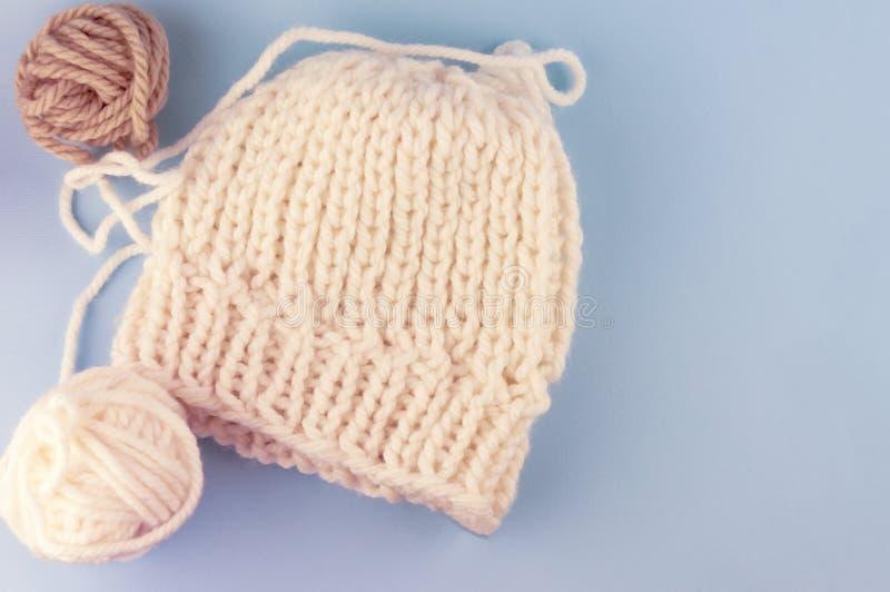 Aiguilles et fil de tricotage de vintage sur un fond bleu, un chapeau attaché avec la laine naturelle blanche Avec la tache floue photographie stock libre de droits