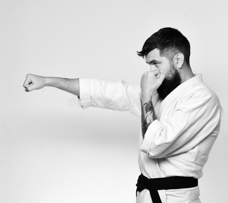 Aikido master with black belt practices defense posture. Healthy lifestyle and sports concept. Man with beard in white kimono on white background. Karate man royalty free stock images