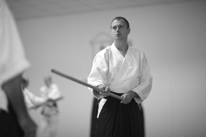 Aikido. Testing of fighting techniques with a sword in aikido royalty free stock photography