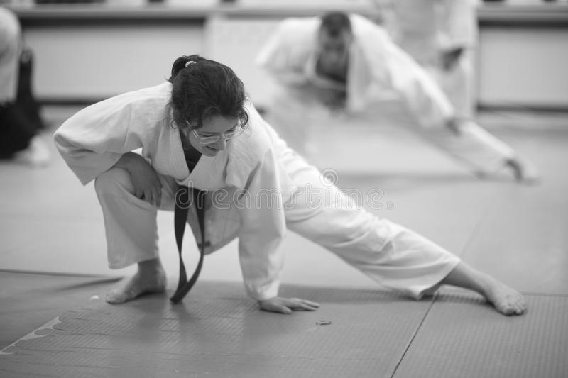 Aikido. Warm-up and stretching of muscles during training Aikido royalty free stock photography