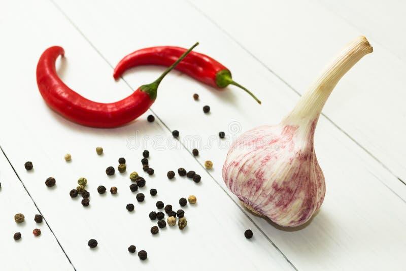 Ail, poivre de piment rouge et m?lange parfum? des poivrons sur une table en bois blanche, ?pic? et la cuisson image stock