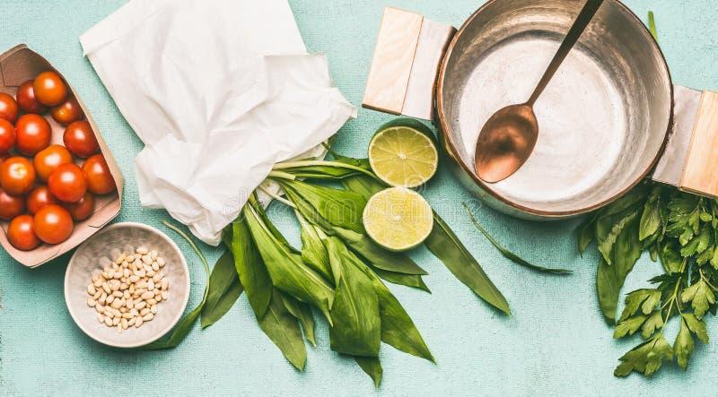 Ail sauvage faisant cuire la préparation : pot avec la cuillère, l'ail sauvage, les pignons, les tomates et l'assaisonnement photographie stock