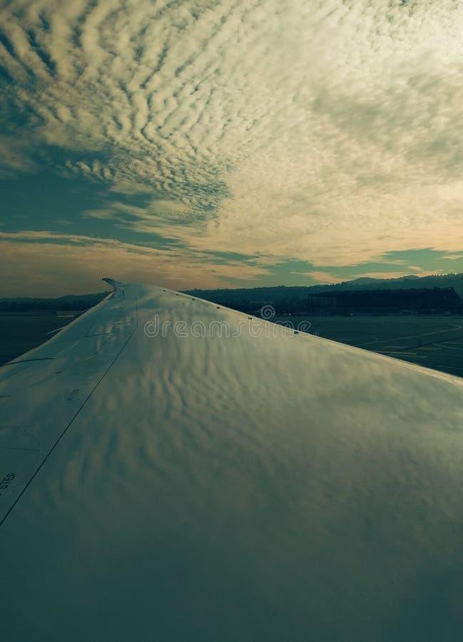 Aile d'avion avec la réflexion onduleuse de nuage photo stock