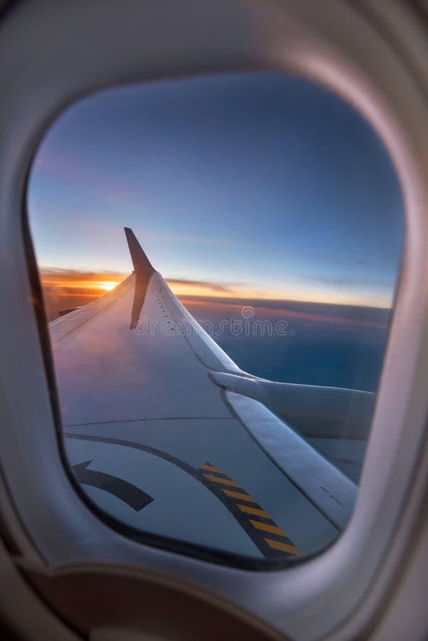 Aile d'avion par la fenêtre pendant un coucher du soleil vibrant photos stock