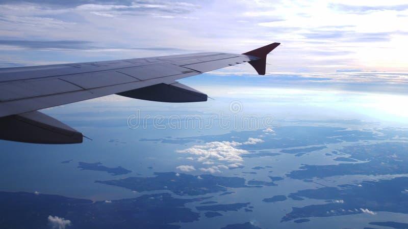 Aile d'un vol d'avion au-dessus des nuages avec le ciel de coucher du soleil Aéronefs image libre de droits
