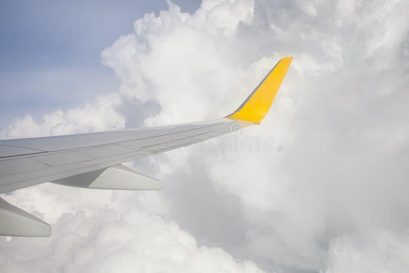 Aile d'un vol d'avion au-dessus des nuages images stock