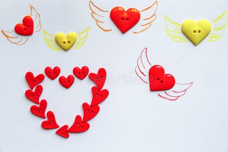 Aile de dessin sur beaucoup de boutons de forme de coeur disposés image libre de droits