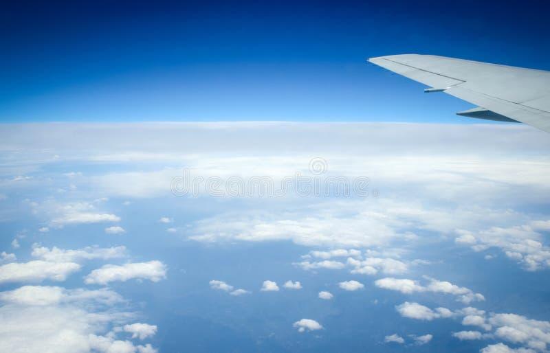 Aile de l'avion sur le fond de ciel bleu et neigeux images stock
