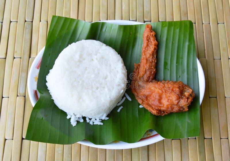 Aile de poulet cuite à la friteuse et riz simple sur la feuille de banane photo stock