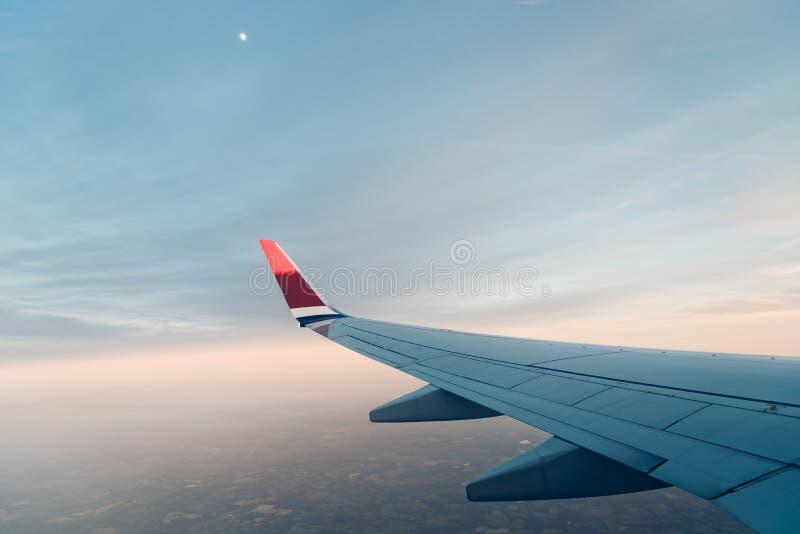 Aile du vol d'avion contre le ciel au coucher du soleil photos stock