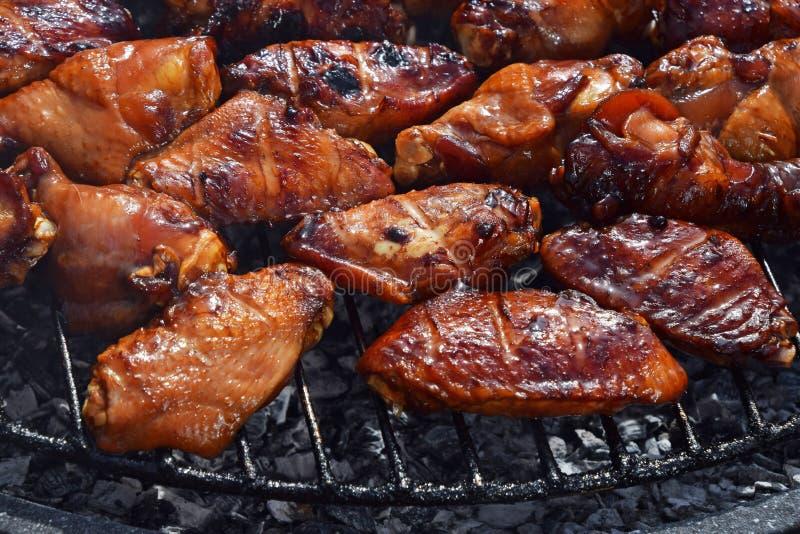 Ailes de buffle de poulet cuites sur le gril de fumée image stock