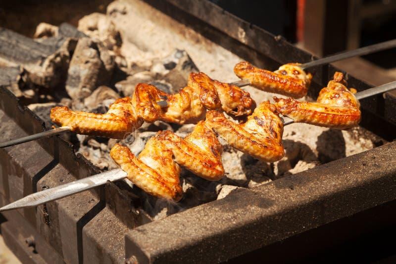 Ailes de poulet de barbecue sur des brochettes étant rôties image stock