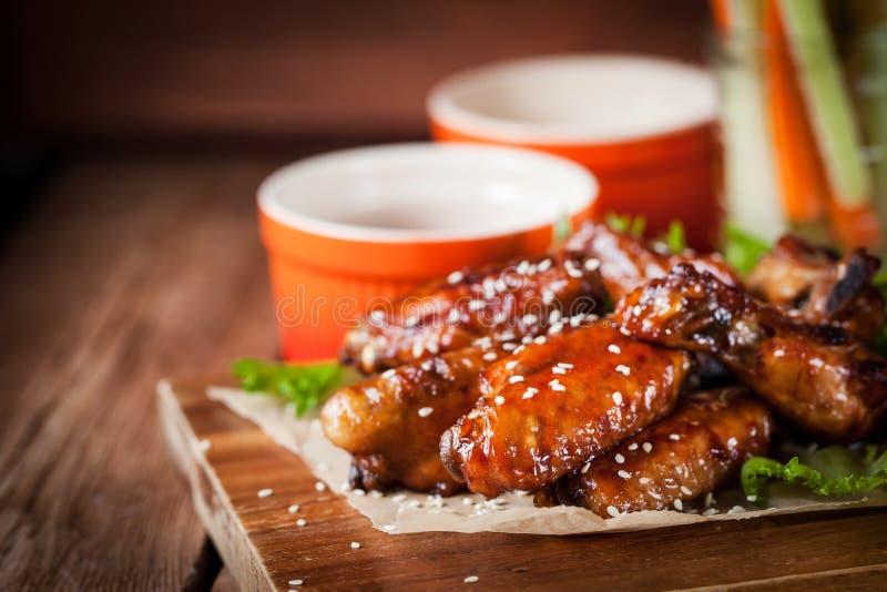 Ailes de poulet chaudes cuites avec du miel et le soja, complétés avec le sésame photographie stock
