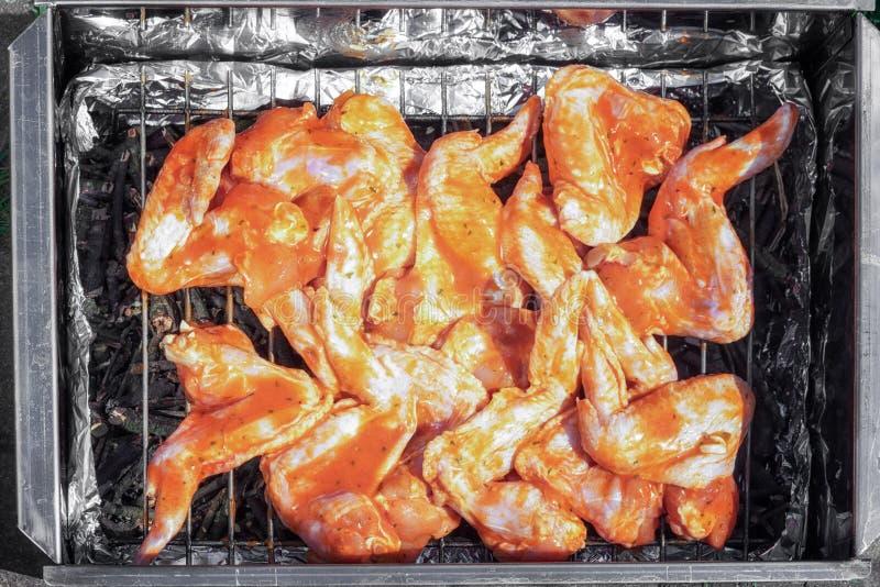 Ailes de poulet crues dans une marinade sur un fumoir photo stock