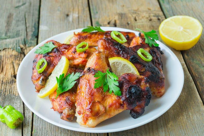 Ailes de poulet cuites au four avec les piments et le citron d'un plat en céramique sur un fond en bois photo stock