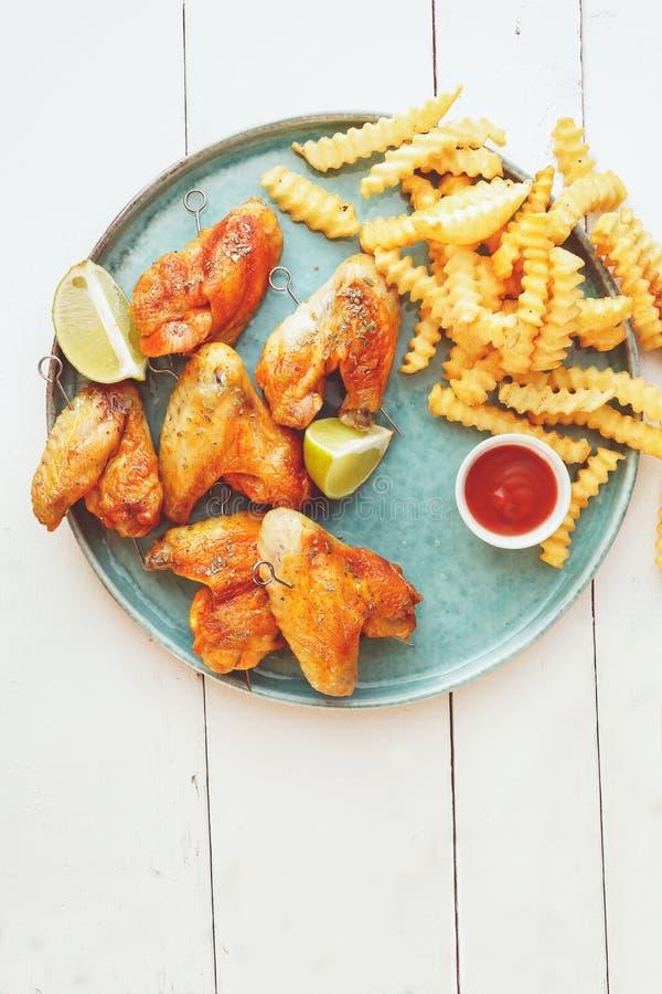Ailes de poulet de barbecue avec les fritures et le ketchup de pomme de terre photographie stock libre de droits