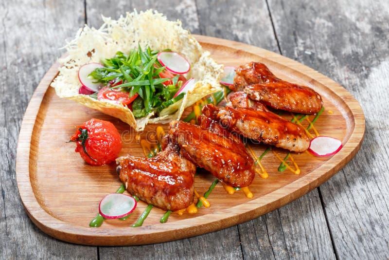 Ailes de poulet frit avec de la salade fraîche, les légumes grillés et la sauce à BBQ sur la planche à découper sur le fond en bo photographie stock libre de droits