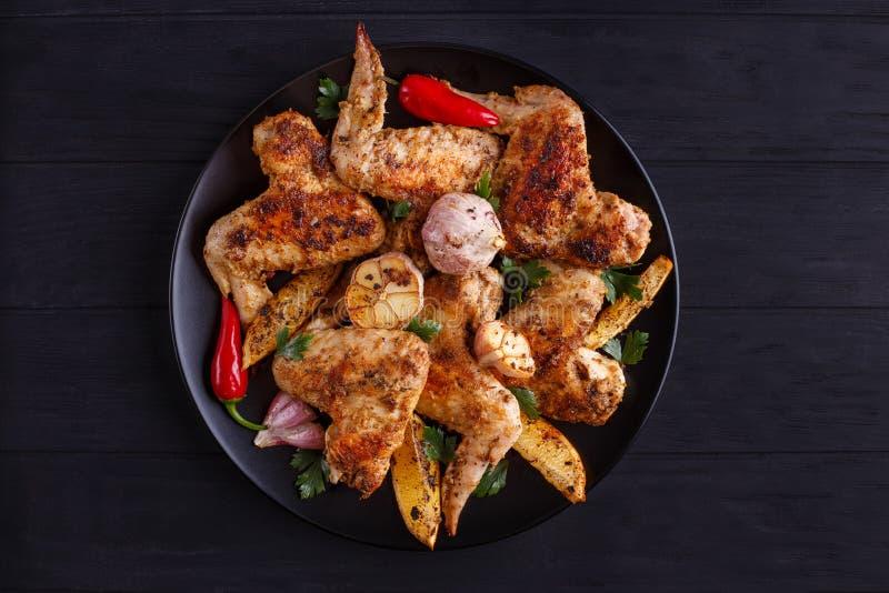 Ailes de poulet grillées avec le citron et l'ail du plat noir cuisinier photographie stock