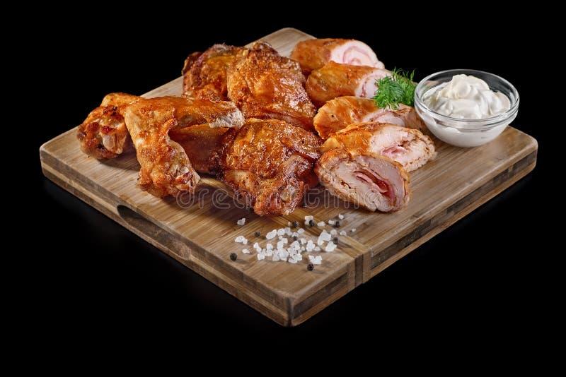 Ailes et jambes de poulet marinées savoureuses de piment, sur le fond noir photo stock