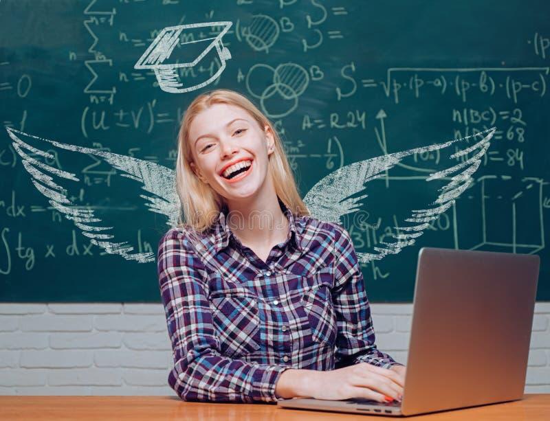 Ailes et rêve d'école ?tudiants adolescents avec le carnet d'?cole Femme travaillant sur l'ordinateur portable au-dessus du table images libres de droits