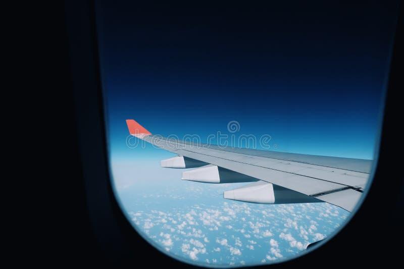 Ailes plates rouges et cieux bleus, vue de fenêtre d'avion images stock