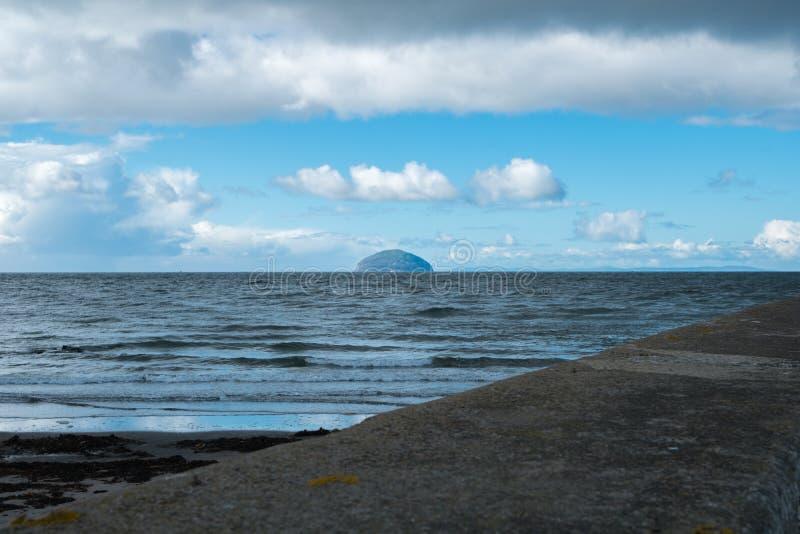 Ailsa Craig & molniga Skys från den Girvan hamnen i Skottland royaltyfri foto